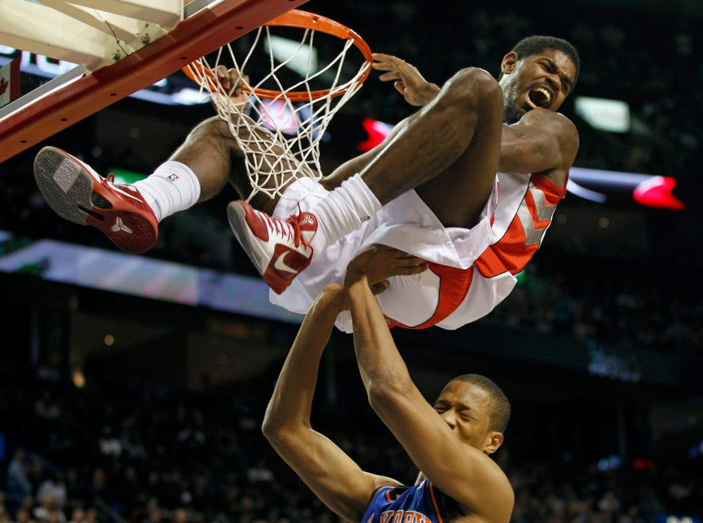 Raptors' Johnson celebrates his slam dunk over Knicks' Randolph during the first half of NBA pre-season action in Montreal